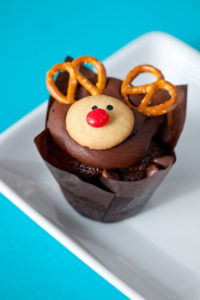 Reindeer Chocolate $3: A chocolate cupcake baked with both semi sweet and milk chocolate chips, topped with a chocolate frosting decorated as a reindeer.