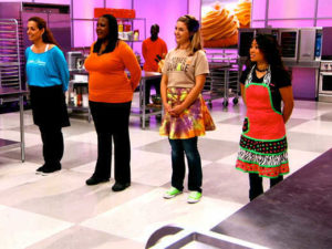 Cupcake Wars competitors stand together as they wait to hear who they will be creating their cupcakes for and the ingredients they will use.