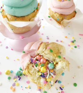 Birthday Surprise $3 - Our classic vanilla cupcake filled with pastel sprinkles and sixlets. Topped with light pink or baby blue buttercream, and more sprinkles!